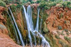 Красивое фото водопада Ouzoud в Марокко с мягкой текущей водой и большими покрашенными утесами Зеленые одичалые джунгли дальше Стоковые Фотографии RF