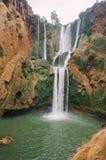 Красивое фото водопада Ouzoud в Марокко с мягкой текущей водой и большими покрашенными утесами Зеленые одичалые джунгли дальше Стоковая Фотография