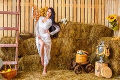 Красивое худенькое брюнет стоя в белом платье в амбаре с сеновалом, концепцией релаксации стоковое фото rf