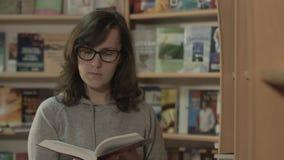 Красивое чтение девушки в библиотеке видеоматериал