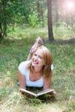 Красивое чтение девушки лежа на траве в whith l леса Стоковые Изображения RF