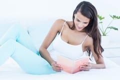 Красивое чтение женщины на ее кровати Стоковые Фотографии RF