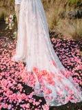 Красивое bridal платье и розовые лепестки после свадебной церемонии стоковое изображение