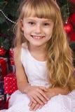 Красивое gir младенца около рождественской елки в Новогодней ночи Стоковое Изображение