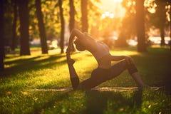 Красивое rajakapotasana представления короля Голубя asana йоги практик молодой женщины в парке на заходе солнца Стоковое фото RF