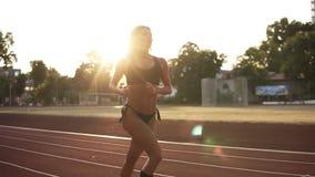Красивое runnung спортсменки, разрабатывая в утре на стадионе Нося черное бикини и белые тапки сток-видео