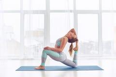 Красивое sporty rajakapotasana представления короля Голубя asana йоги практик женщины yogi пригонки на студии йоги Стоковые Фото
