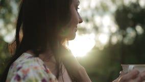 Красивой женщина постаретая серединой выпивает чай outdoors видеоматериал