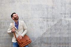 Красивой парень постаретый серединой стоя против стены стоковая фотография