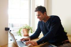 Красивой человек постаретый серединой с компьтер-книжкой дома стоковое фото rf