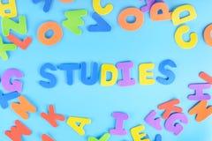 Красиво положенные вне исследования надписи пестротканых писем предпосылка яркая Стоковые Изображения RF