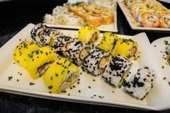 Красиво представленный и свеже подготовленный сладостный крен суш манго служил на белой плите, черной таблице Стоковые Изображения
