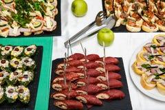 Красиво украшенная поставляя еду таблица банкета с различными закусками и закусками еды на корпоративном событии вечеринки по слу стоковые фото