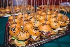 Красиво украшенная поставляя еду таблица банкета с различными сандвичами бургеров гамбургеров на плите на корпоративном birthd ро стоковое фото rf