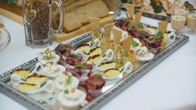 Красиво украшенная поставляя еду таблица банкета с различными закусками и закусками еды на корпоративном дне рождения рождества сток-видео