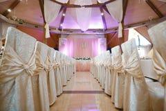 Красиво украшенные смычки таблицы и стульев для свадебной церемонии Служат украшенная таблица банкета дизайн концепции залы стоковое изображение