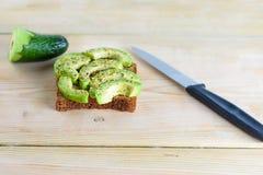 Красиво хлеб тоста рож с отрезанным зеленым авокадоом стоковое фото
