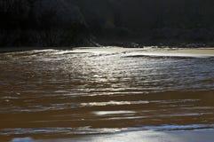 Красиво patterened влажный песок отражая голубое небо silhouetted темными скалами Стоковая Фотография RF