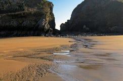 Красиво patterened и расколотый влажный песок отражая голубое небо silhouetted темными скалами Стоковое Изображение RF