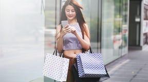 Красивые азиатские девушки с хозяйственными сумками используя smartphone Стоковая Фотография