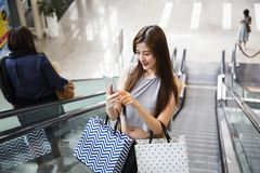 Красивые азиатские девушки с хозяйственными сумками используя smartphone Стоковые Изображения