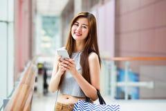 Красивые азиатские девушки с хозяйственными сумками используя smartphone Стоковое Изображение RF