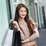 Красивые азиатские девушки с хозяйственными сумками Стоковые Фото