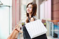 Красивые азиатские девушки с хозяйственными сумками Стоковые Изображения RF