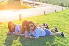 Красивые азиатские девушки кладя на зеленую траву под солнечным светом, w Стоковое Изображение RF