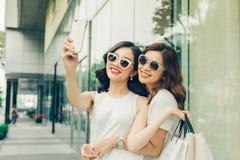Красивые азиатские девушки при хозяйственные сумки принимая фото selfie на Стоковая Фотография RF