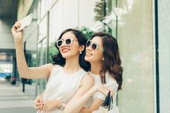 Красивые азиатские девушки при хозяйственные сумки принимая фото selfie на Стоковые Фотографии RF