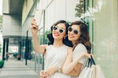 Красивые азиатские девушки при хозяйственные сумки принимая фото selfie на Стоковое фото RF