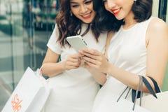 Красивые азиатские девушки с хозяйственными сумками используя smartphone на Стоковые Фото