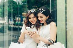 Красивые азиатские девушки с хозяйственными сумками используя smartphone на Стоковое Фото