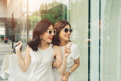 Красивые азиатские девушки с хозяйственными сумками идя на улицу на th Стоковые Фото