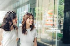 Красивые азиатские девушки с хозяйственными сумками идя на улицу на th Стоковое фото RF