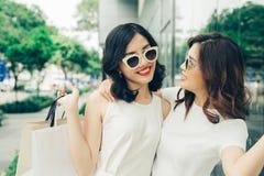 Красивые азиатские девушки с хозяйственными сумками идя на улицу на th Стоковая Фотография RF