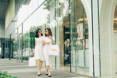 Красивые азиатские девушки с хозяйственными сумками идя на улицу на th Стоковые Фотографии RF