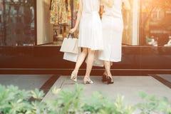 Красивые азиатские девушки с хозяйственными сумками идя на улицу на th Стоковое Фото