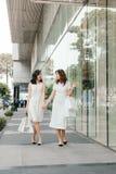 Красивые азиатские девушки с хозяйственными сумками идя на улицу на th Стоковая Фотография