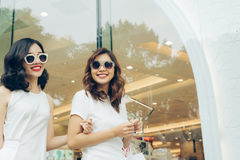 Красивые азиатские девушки с хозяйственными сумками идя на улицу Стоковые Изображения