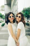 Красивые азиатские девушки с хозяйственными сумками идя на улицу Стоковое Изображение RF