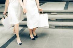 Красивые азиатские девушки с хозяйственными сумками идя на улицу Стоковые Фото