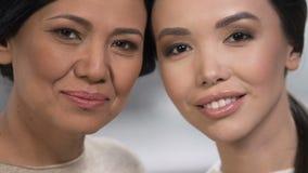Красивые азиатские женщины усмехаясь на камере, против старения косметики, крупный план стороны акции видеоматериалы