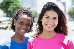 Красивые африканские и кавказские женщины в городе Стоковое фото RF