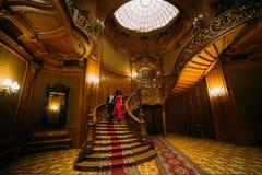 Красивые африканские пары идя вниз на винтажные лестницы Роскошная предпосылка интерьера театра стоковые фото