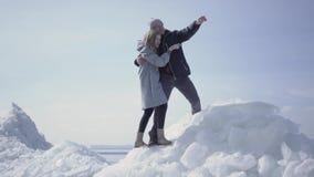 Красивые белокурые пары указывая отсутствующий обнимая один другого Бородатый человек в стеклах и привлекательной женщине восхища сток-видео