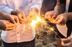 Красивые бенгальские огни в концепции рук, xmas и Нового Года людей стоковое фото rf