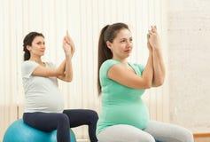 Красивые беременные женщины делая йогу на шариках Стоковое Изображение RF