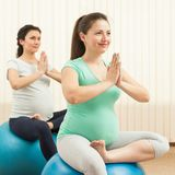Красивые беременные женщины делая йогу на шариках Стоковые Изображения RF